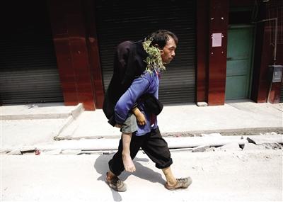 昨日,云南省洛泽河镇龙潭村大苗寨,村民王明才将去世的10岁孙子背回家。新京报记者 郭铁流 摄