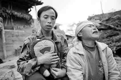 代课老师朱银全拿着遇难学生的书包,劝慰伤心痛哭的死者母亲。