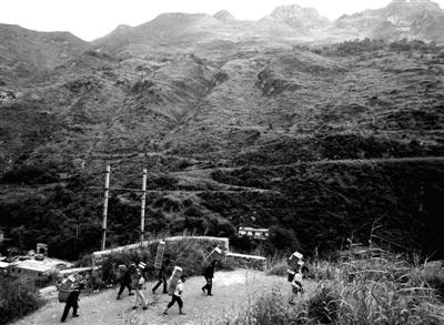 昨日,昭通市洛泽河朱家营的村民往山上搬运救灾食品。他们在这条路上来回一趟要走6小时。本版图片/新京报记者 郭铁流 摄