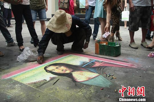 9月9日,一名乞丐在重庆市沙坪坝区步行街上,头戴草帽身穿一袭破旧蓝衣在地上正画《蒙娜丽莎的微笑》。