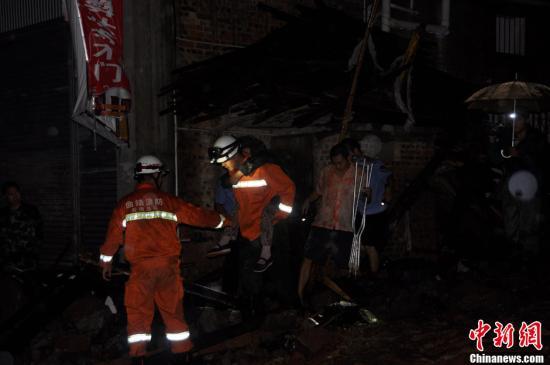 11日凌晨,昭通市彝良县震后突降暴雨引发城区洪涝和泥石流灾害,灾情十分危急。图为消防官兵冒雨解救被困群众。赖应博 摄