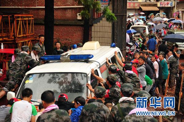 9月11日,在云南彝良县医院前,人们把救护车从淤泥中拉出来。