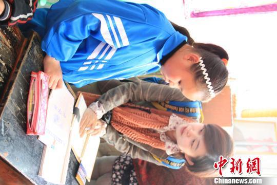 女孩 杨茜摄/12岁的藏族女孩卓玛向到访的中新社记者背诵唐诗《早发白帝城》...