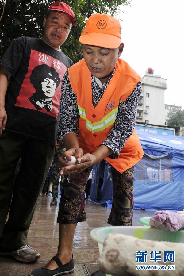9月12日,刘光建在摆放脸盆、帕子,给过往的群众提供方便。