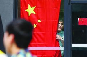 威海日资企业佳世客商场暂停营业,一位店员透过玻璃门向外观望着。
