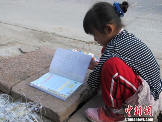 图为马江的小孙女正在院子里的一块石板上看书。宋锦丰摄