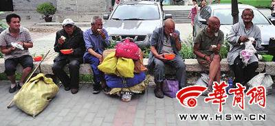 """流浪者坐在台阶上吃着""""黄河慈善厨房""""提供的饭食 本版图片由本报记者 陈团结 摄"""