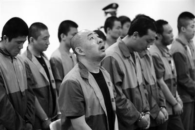 """昨日,海淀法院,北京今年最大的非法组织卖血案开庭,12名被告人均表示认罪。其中,""""血头""""王海涛(前排左一)称,作案是为救助患病的弟弟。通讯员 李森 摄"""