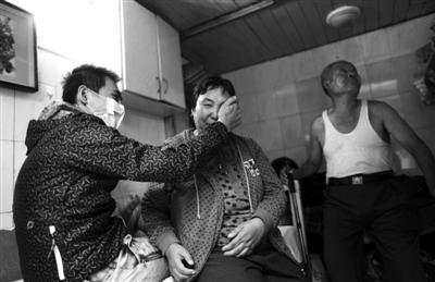 昨日,租住的小屋里,身患白血病的王海福给母亲擦眼泪,其父站在他们身后。新京报记者 薛�B 摄