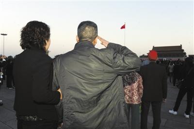 昨日,天安门广场。老兵喻彬和妻子一起看升国旗,向国旗敬礼。新京报记者 尹亚飞 摄