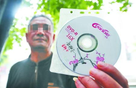 昨日,沙坪坝区天梨路,付登国展示老伴拿回来的宣传光碟。 记者 吴珊 摄