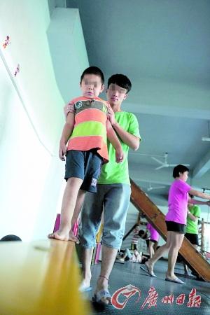 番禺子惠儿童康复中心的老师们正在教自闭症儿童练习身体的协调性.