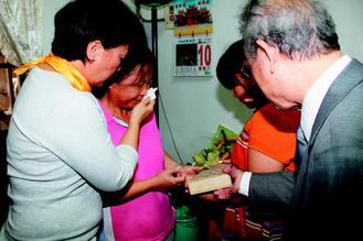 江的两个妹妹(左二、三)接过遗书,难过的掉泪,龙应台(左)替她们拭泪。台湾《联合报》