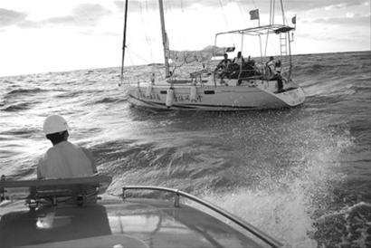 救助船靠近遇险帆船准备实施救援