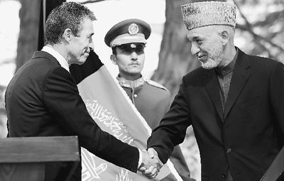 10月18日,在阿富汗喀布尔,北约秘书长拉斯穆森(左)与阿富汗总统卡尔扎伊结束联合新闻发布会后握手。