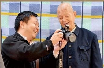 李明顺给75岁老人牛德祥看拍摄的照片。