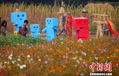 10月28日,两位市民在田园中被各种创意小品吸引.中新社发 泱波 摄