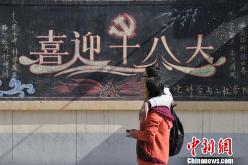 的黑板报前走过.韦亮 摄-山西高校学子办黑板报迎接 十八大