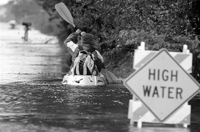 """当地时间10月28日,美国弗吉尼亚州,飓风""""桑迪""""引发洪水,当地居民乘舟逃离危险水域。"""
