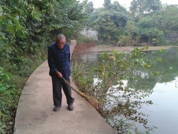 11月5日下午,汪林炳大爷在三岔湖边扫地。