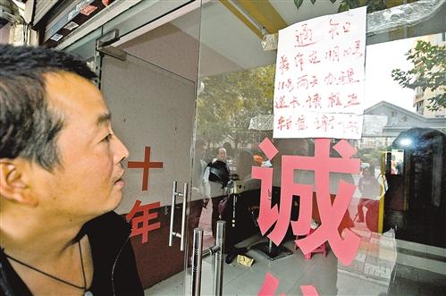 马玉剑/11月12日,理发店附近居民观看马玉剑在理发店玻璃门上贴的退...