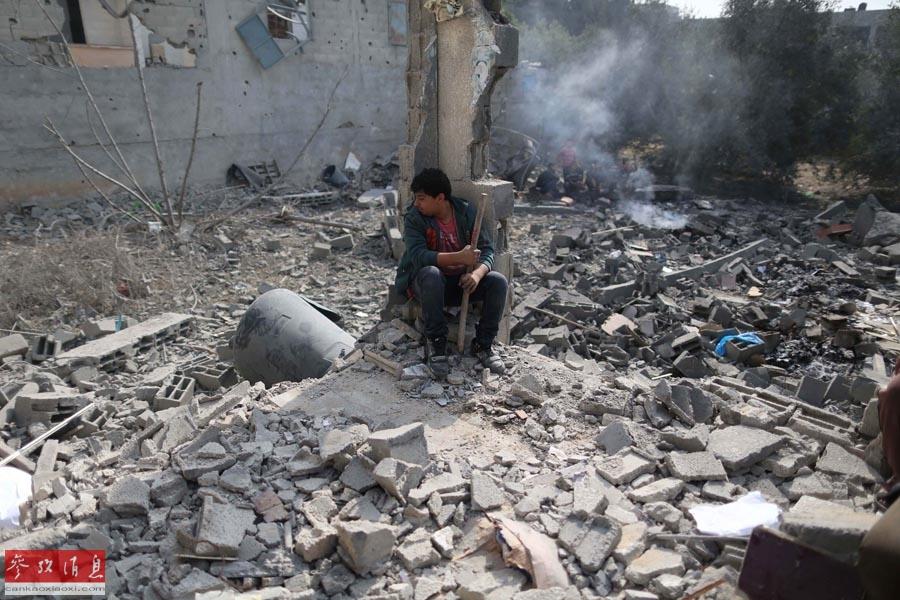 11月17日,在加沙城北部的杰巴利耶难民营,一名巴勒斯坦人坐在空袭后