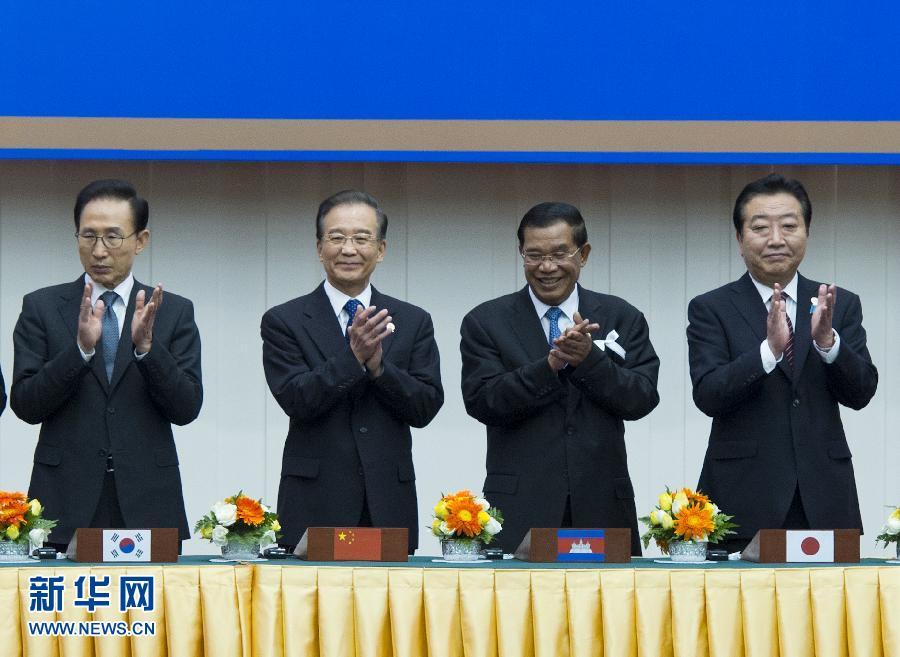 """11月19日,东盟与中日韩(10+3)合作15周年纪念峰会在柬埔寨金边""""和平宫""""举行。国务院总理温家宝出席。这是与会领导人合影。新华社记者王晔摄"""