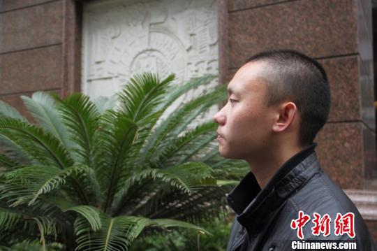 图为任建宇11月20日下午14时许在重庆第三中级人民法院门前等待进入法庭。刘贤摄