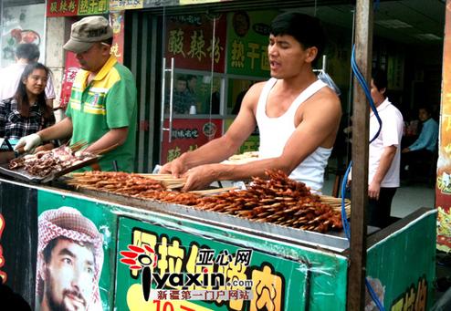 深圳/11月17日,新疆小伙买买提在深圳边烤烤肉边跳舞。