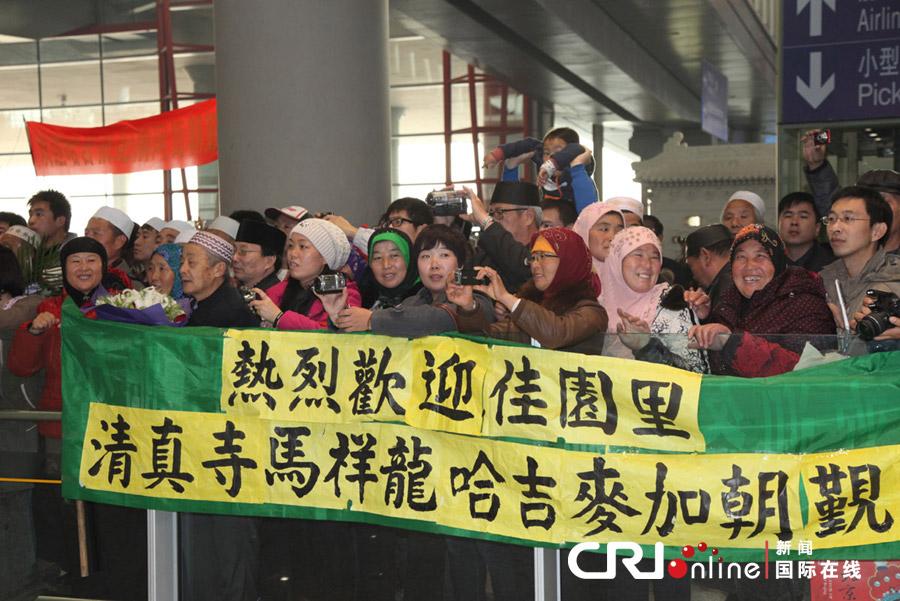 中国 肖中仁/前来迎接朝觐归国人员的亲友们打起了横幅影:肖中仁