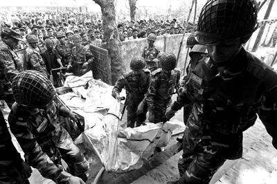 25日,军方救援人员将火灾遇难者遗体抬出起火厂房。