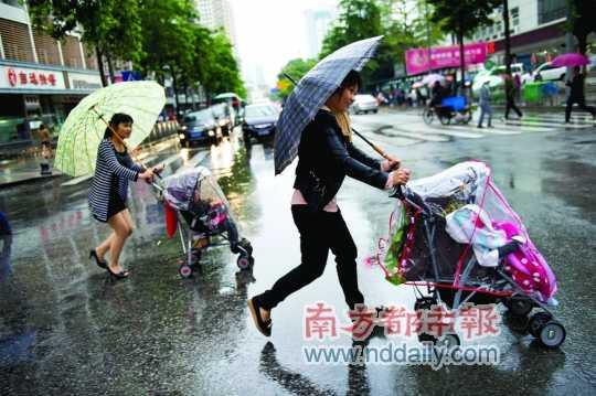 深圳/华新地铁站外,冷雨越下越大,一个小女孩紧紧地靠在妈妈身上。