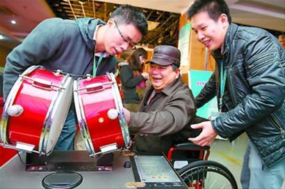 """中国 科技馆 流动/一位残疾观众在志愿者陪伴下参观""""流动科技馆""""的科普展品。"""