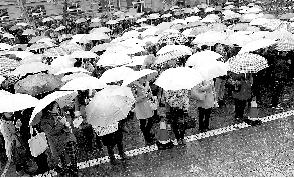 11月25日,南京林业大学考点的考生在考场外冒雨等待进入考场。新华社发