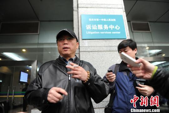 李庄在重庆第一中级人民法院立案大厅前接受媒体采访。陈超摄