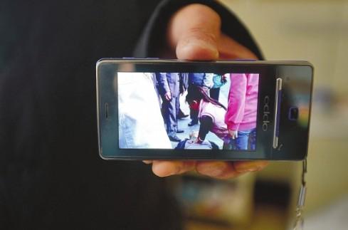 视频记录感人一幕 本报记者 翟剑 翻拍