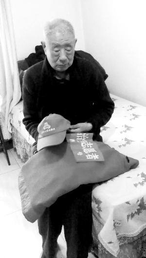 宫龙江老人整理着老伴执勤时的衣物。雷娟丽/摄