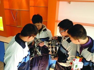 4个孩子在摆弄他们的机器人。 谷岳飞 摄