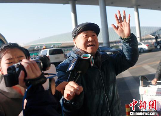 12月5日,莫言从北京首都机场出发启程赴瑞典。图为莫言下车进入机场贵宾室前挥手。中新社发 张浩 摄