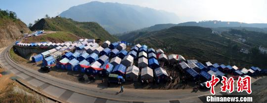 图为技术人员现场指导村民重建新房。彭洪摄