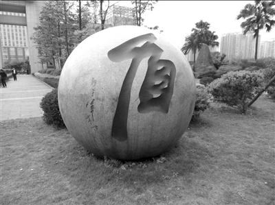 """重庆市公安局门口的石球上,原局长王立军昔日题写的""""盾""""字如今已经消失。"""