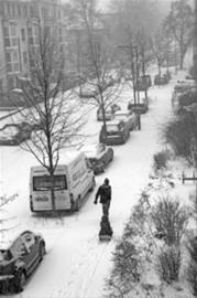 12月9日,在德国柏林市东北潘科夫区,一位父亲拉着孩子乘坐的雪橇行走在大雪中。