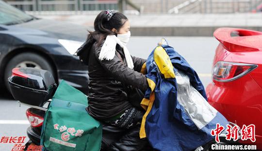 12月11日,一位穿着厚实的送报人员骑行在长沙街头。中新社发 杨华峰 摄