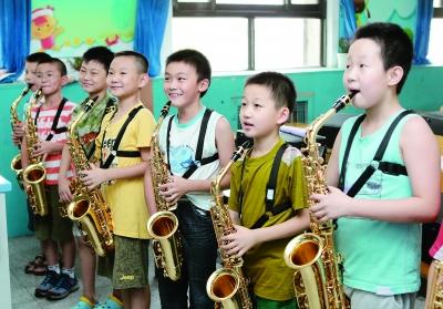 中关村三小管乐团的同学们认真听取老师的指导。 本报记者 卢 旭 摄