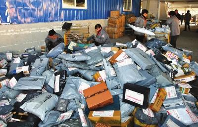12月12日,快递员在江苏省南通市一家快递 公司的派送件现场分拣快件.