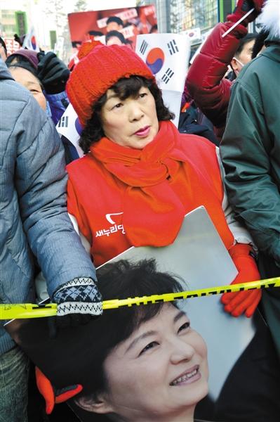 12月13日,韩国执政党新国家党总统候选人朴槿惠举行竞选活动时,一支持者手持其画像。