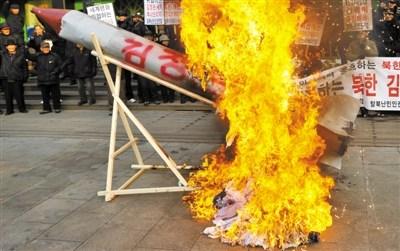 韩国/13日,韩国首尔,一些民众焚烧火箭模型,对朝鲜发射卫星表示...
