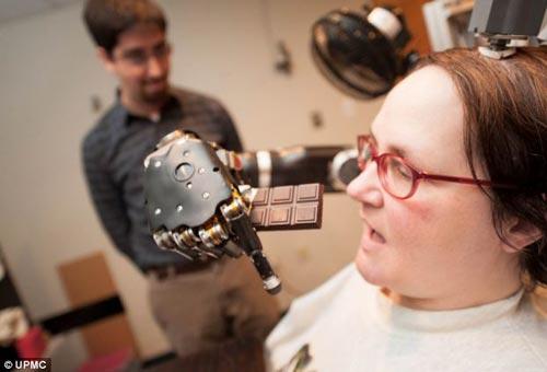 研究人员在她的大脑内置入两个电极,从而能够比其他系统更精准地控制机械手臂