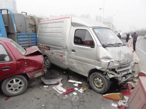 """前面5辆车正在等红灯,却被后面1辆拉水的货车追尾,6辆车""""穿糖葫芦""""般连在一起,其中1辆夏利车被夹在中间,车身严重变形。事故导致快速路堵车300多米。"""
