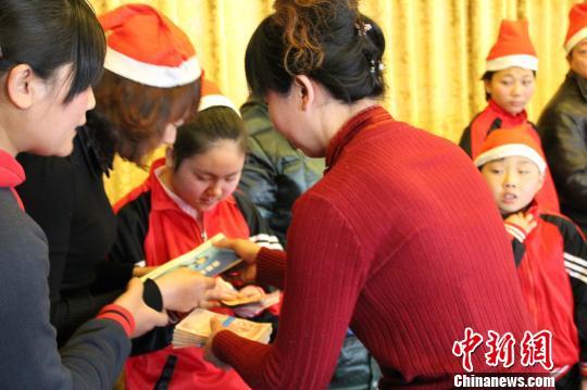 图为张家口市育宝特殊儿童康复中心主任张素霞为自闭症贫困儿童家庭发放救助款 宋锦丰 摄